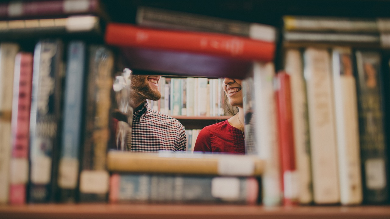 Two people at library behind books - Image provided by author