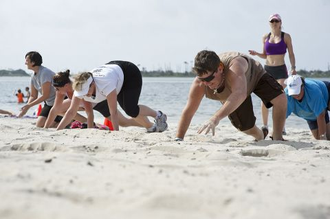 Participants of a beach boot camp class crawl across Soundside Beach at Hurlburt Field, Fla., May 18, 2013. The class combined a number of physical challenges and obstacles designed to push people past their physical limits.
