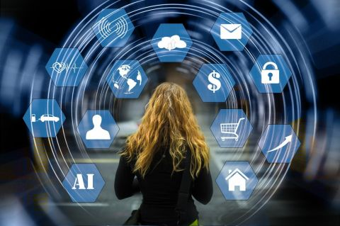 Woman standing in front of virtual screen with multiple icons