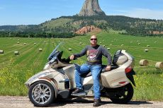 Bryan Ruby sitting on a Can-Am Spyder RT Limited near Devil's Tower